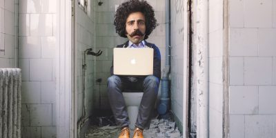 Man sitting on toilet with laptop