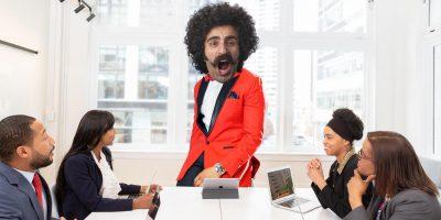 Man wearing bright orange blazer in office meeting